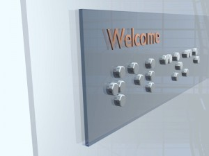 Welcome sign with Braille characters. Glass sign on a glass door.